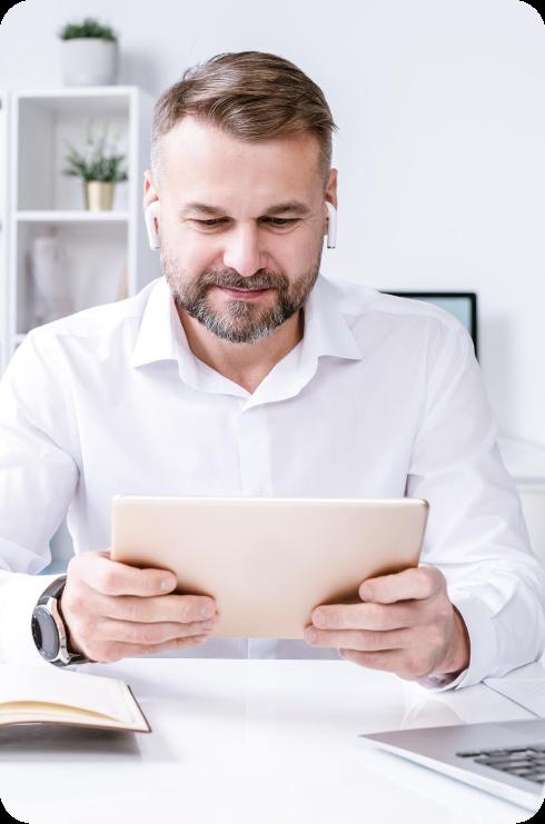 Ein bärtiger Mann hält ein Tablet in seiner Hand und liest.