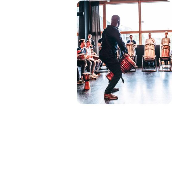 Bei einem Trommelworkshop als Team-Event trommeln alle Mitarbeiter von karriere tutor® denselben Rhythmus