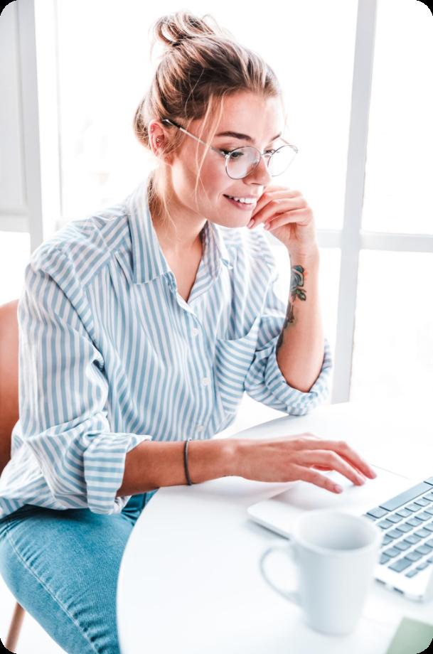Eine lächelnde Frau macht eine Weiterbildung mit Bildungsgutschein am Laptop