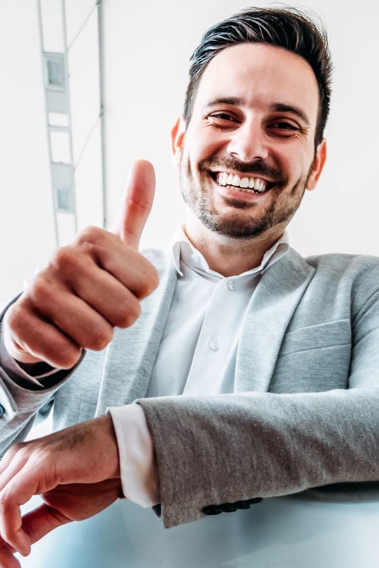 Ein Mann freut sich über eine Weiterbildung mit Bildungsgutschein und zeigt mit dem Daumen nach oben