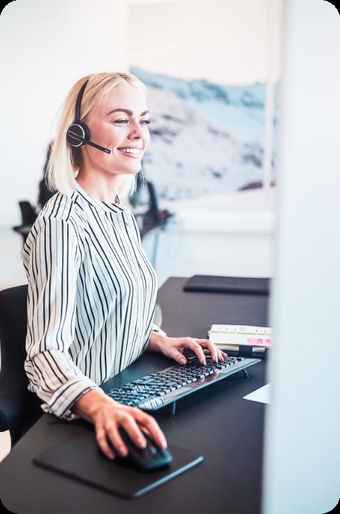 Eine lächelnde Frau mit Headset sitzt vor einem PC an einem karriere tutor®-Standort und lernt.