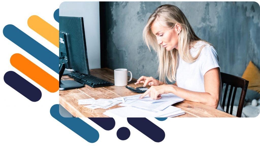 Eine Frau sitzt an einem Schreibtisch, auf dem ein PC steht, und recherchiert nach Foerderungen fuer ihre Weiterbildung.