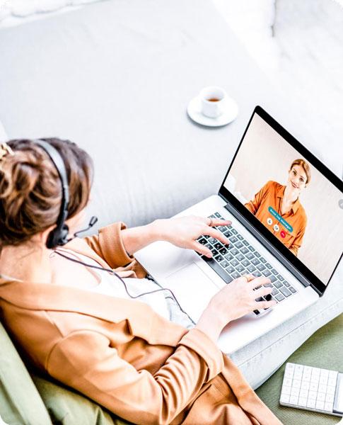 Eine Frau mit Headset sitzt vor ihrem Laptop und kommuniziert mit einem Dozenten