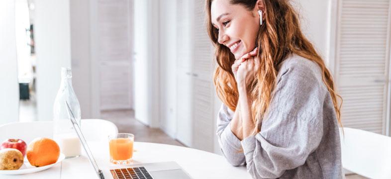 Eine lächelnde Frau mit In-Ear-Kopfhörer sitzt im Homeoffice vor einem Laptop und hat ein Glas Saft neben sich stehen